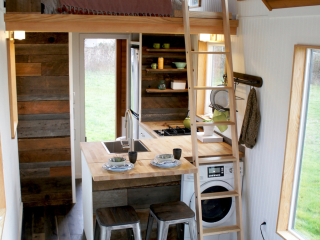 tiny home with wheels in dining and bedroom nook with ladder
