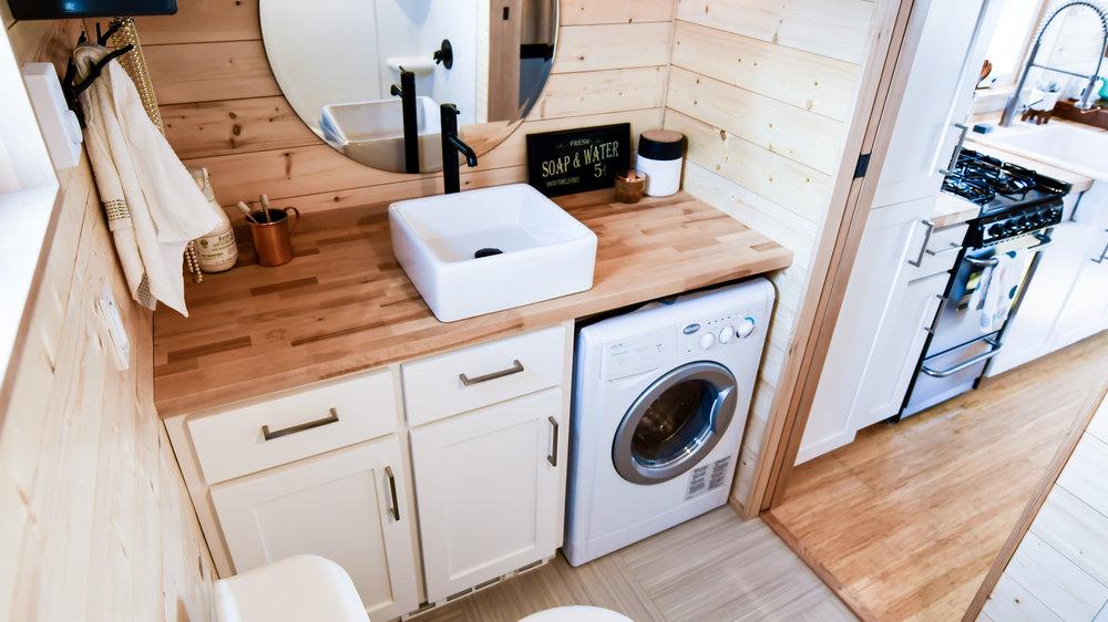 tiny bathroom sink with laundry machine